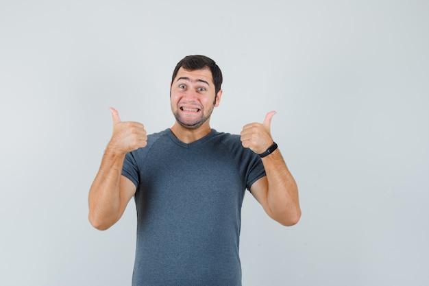 Jonge man dubbele duimen opdagen in grijs t-shirt en vrolijk kijken