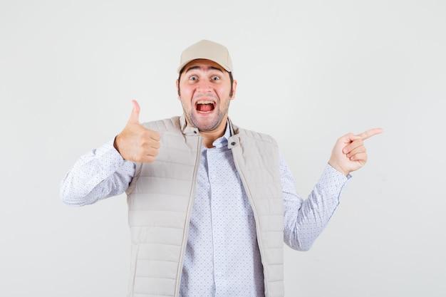 Jonge man duim opdagen en naar rechts wijzend met wijsvinger in beige jas en pet en op zoek gelukkig, vooraanzicht.