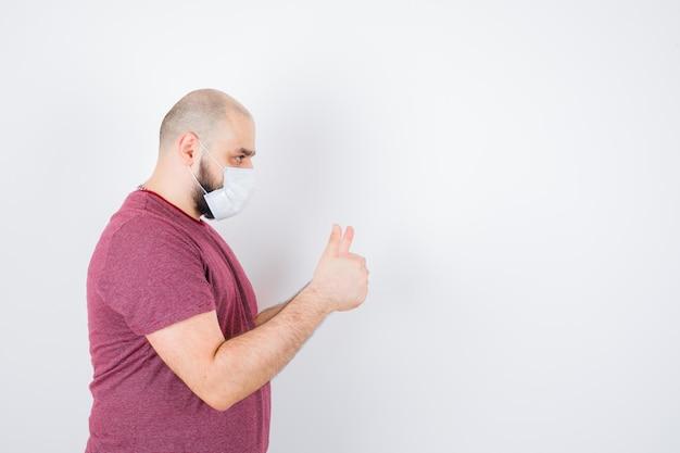 Jonge man duim opdagen in roze t-shirt, masker en op zoek gefocust. . ruimte voor tekst
