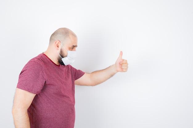 Jonge man duim opdagen in roze t-shirt, masker.
