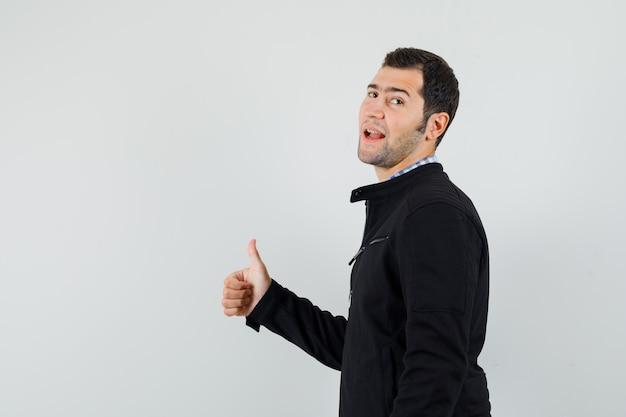 Jonge man duim opdagen in shirt, jasje en op zoek zelfverzekerd.