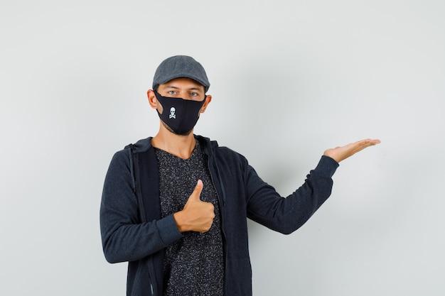 Jonge man duim opdagen, palm opzij spreiden in t-shirt, jas, pet, masker