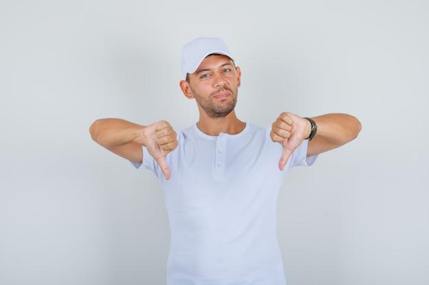 Jonge man duimen omlaag in wit t-shirt, pet en op zoek naar ontevreden, vooraanzicht.
