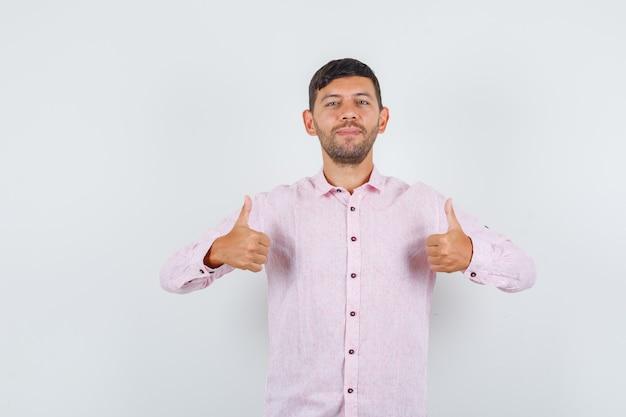 Jonge man duimen opdagen in roze shirt en op zoek zelfverzekerd, vooraanzicht.