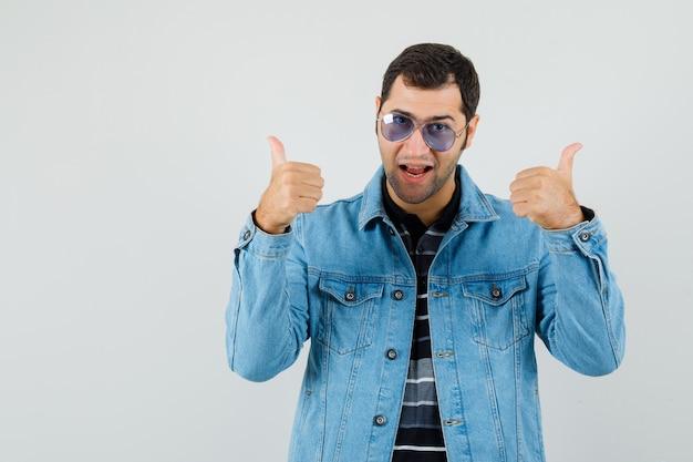 Jonge man duimen opdagen in t-shirt, jasje en op zoek vrolijk. vooraanzicht.