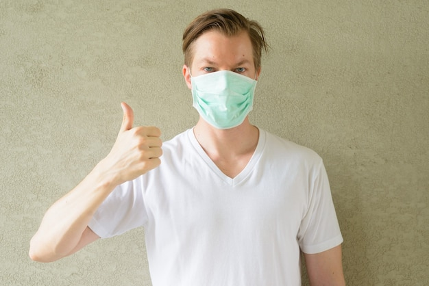 Jonge man duimen opgevend en masker dragen ter bescherming tegen uitbraak van het coronavirus