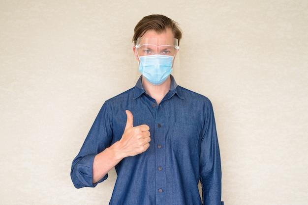 Jonge man duimen opgevend met masker en gelaatsscherm op betonnen muur