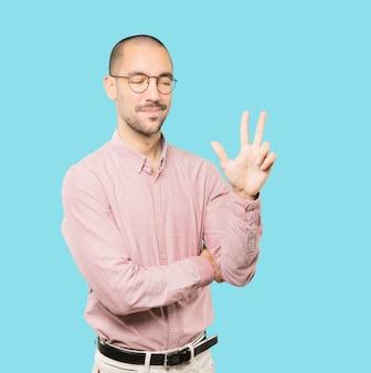 Jonge man een nummer drie gebaar maken