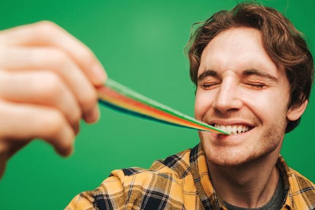 Jonge man eet gelei snoep met plezier, geïsoleerd op groene achtergrond.