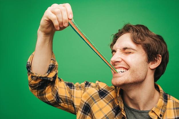 Jonge man eet geleisuikergoed met plezier