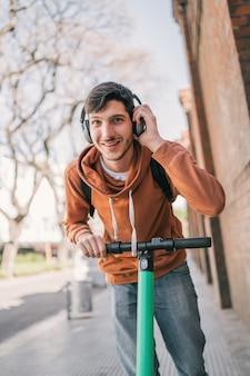 Jonge man elektrische scooter rijden.