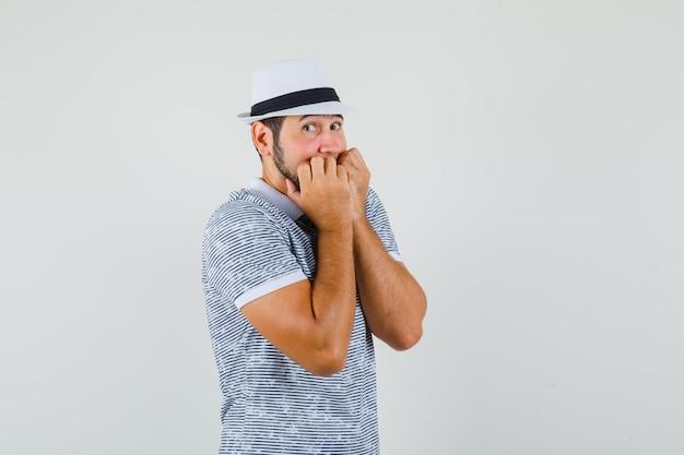 Jonge man emotioneel nagels bijten in t-shirt, hoed en bang kijken. vooraanzicht.