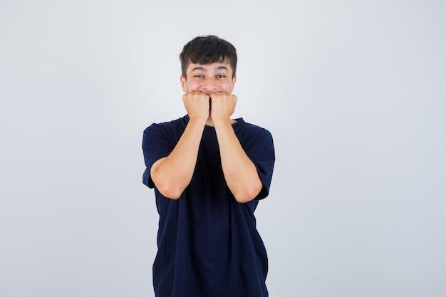 Jonge man emotioneel vuisten bijten in zwart t-shirt en bang op zoek. vooraanzicht.