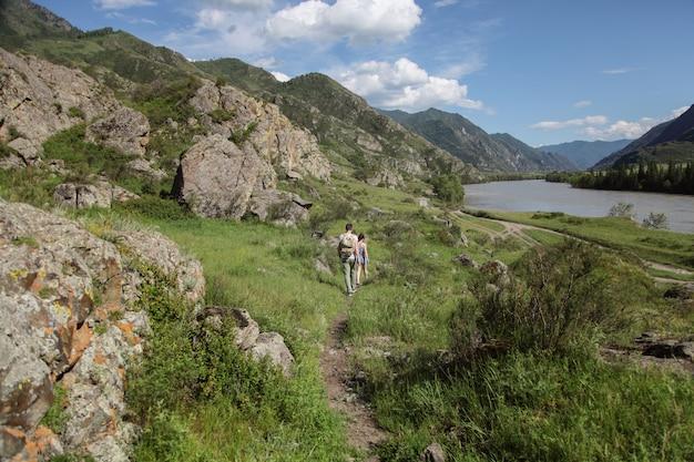 Jonge man en de vrouw gaan langs de bergweg.