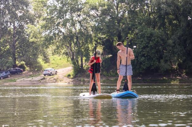 Jonge man en een jonge vrouw paddleboarden op een rivier