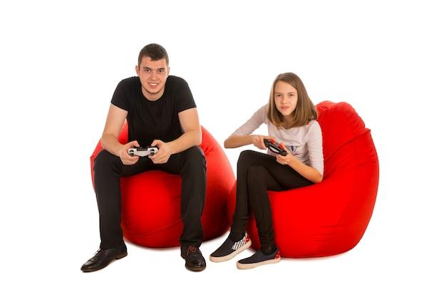 Jonge man en grappig meisje spelen van videospellen zittend op rode zitzak stoelen geïsoleerd op wit