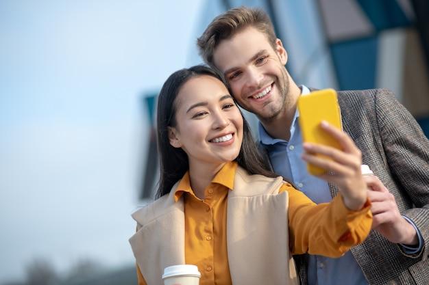 Jonge man en jonge vrouw die gelukkig glimlachen naar de camera tijdens het maken van selfie