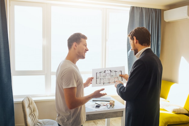 Jonge man en makelaar kopen of huren appartement. ze houden één plan bij elkaar.