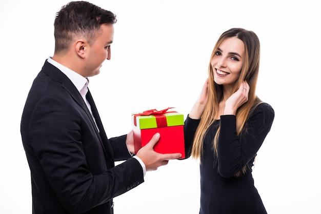 Jonge man en meisje paar onverwachte huidige gift in rode doos op wit