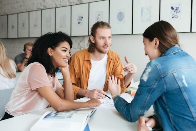 Jonge man en twee dames werken samen in kantoor