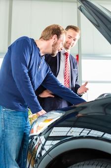 Jonge man en verkoper met auto in het autohandel drijven