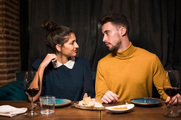 Jonge man en vrouw aan tafel met glazen wijn en eten in restaurant