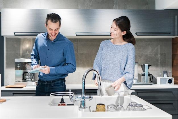 Jonge man en vrouw afwassen in de keuken met een glimlach