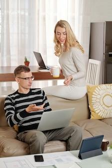 Jonge man en vrouw bespreken informatie op laptopscherm wanneer ze thuis blijven vanwege pandemie
