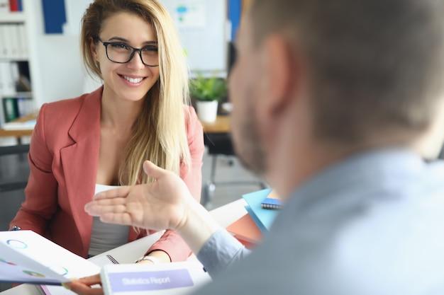 Jonge man en vrouw bespreken met grafieken in hun handen