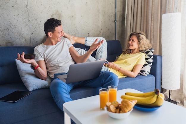 Jonge man en vrouw blijven alleen thuis zittend op de bank met behulp van apparaten die online werken