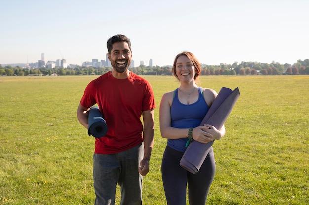 Jonge man en vrouw buiten met yogamatten