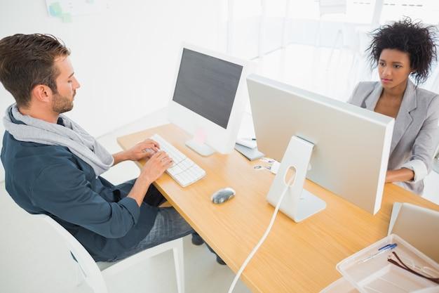 Jonge man en vrouw die aan computers werken