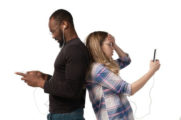Jonge man en vrouw die apparaten gebruiken