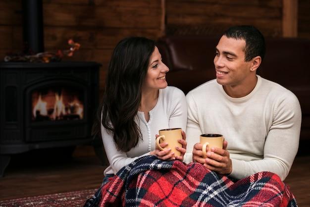 Jonge man en vrouw die bij elkaar glimlachen