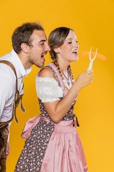 Jonge man en vrouw die een grillvork houden