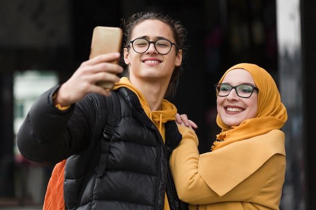 Jonge man en vrouw die een selfie samen nemen
