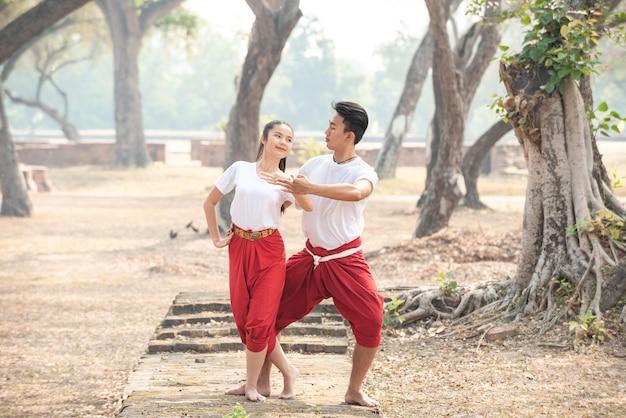 Jonge man en vrouw die een traditionele thaise dans uitoefenen