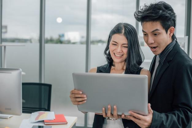 Jonge man en vrouw die laptop gebruikt en naar laptop kijkt