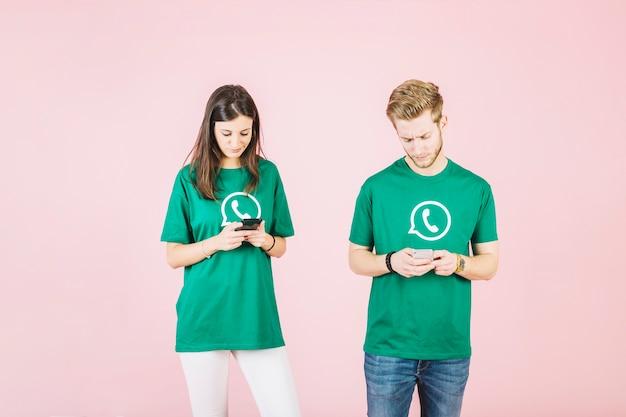 Jonge man en vrouw die mobiele telefoon op roze achtergrond met behulp van