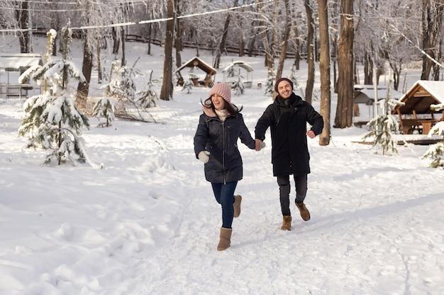 Jonge man en vrouw die op een besneeuwd winterpark lopen