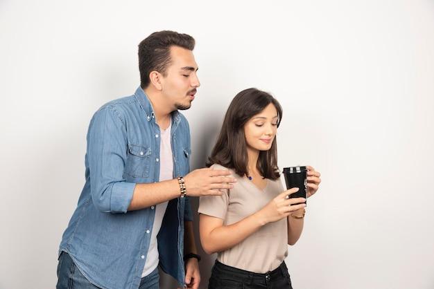 Jonge man en vrouw die op een kop van koffie kijken.