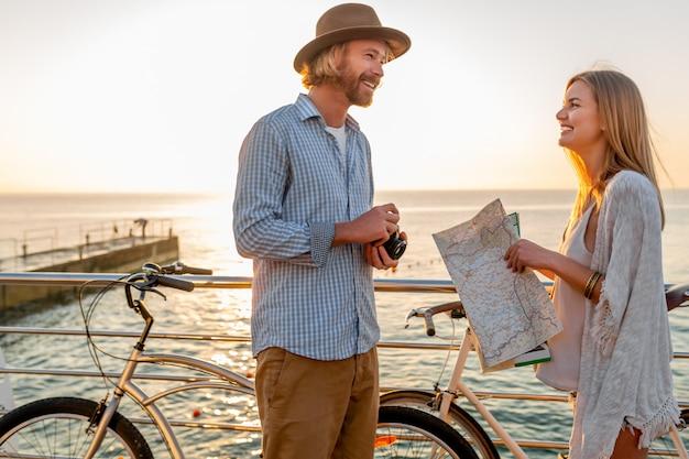 Jonge man en vrouw die op fietsen reizen die kaart houden
