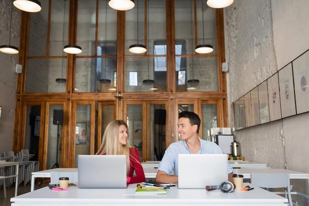 Jonge man en vrouw die op laptop in open ruimte co-working kantoorruimte werkt,
