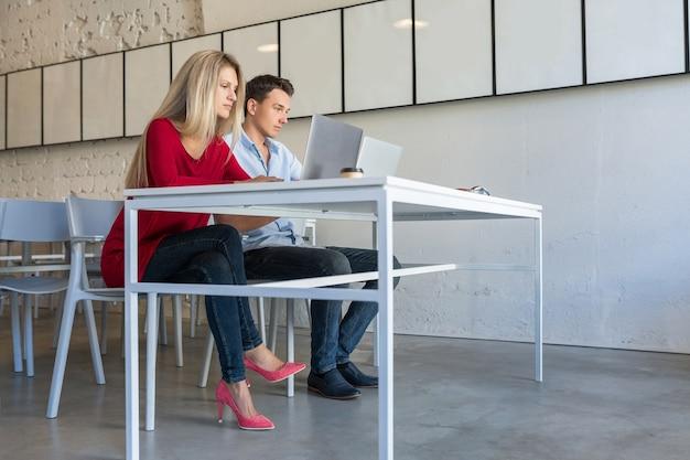 Jonge man en vrouw die op laptop in open ruimte samenwerken kantoorruimte werken
