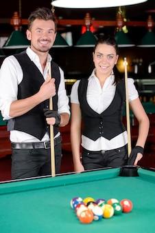 Jonge man en vrouw die professioneel biljart spelen.