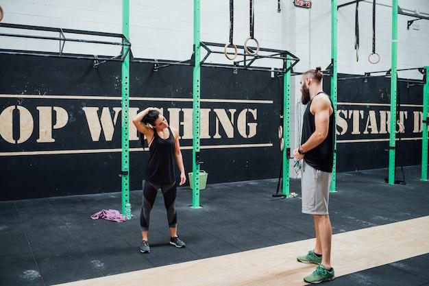 Jonge man en vrouw die samen binnengymnastiek opleiden