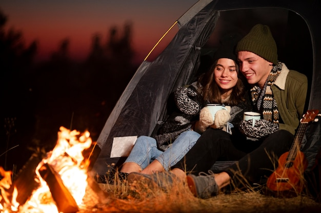 Jonge man en vrouw die van een vuur genieten