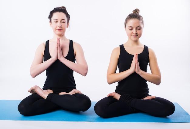 Jonge man en vrouw die yoga doen en in lotusbloempositie mediteren die op wit wordt geïsoleerd