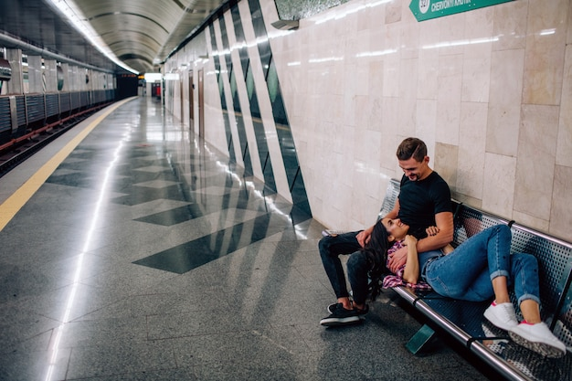 Jonge man en vrouw gebruiken ondergronds. koppel in de metro. jonge vrouw die op het dutje van de kerel ligt. hij kijkt haar aan en omhelst. liefde op het eerste gezicht. valentijnsdag. liefdesverhaal.