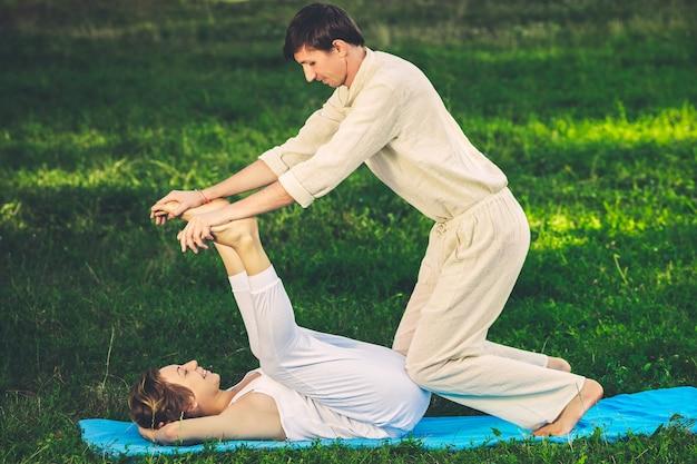 Jonge man en vrouw gekleed in een wit gewaad doen thaise massage met yoga-oefeningen liggend op de mat